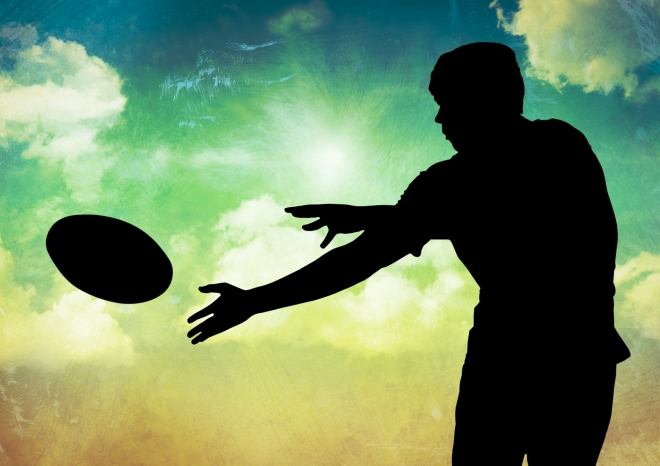 Silhouette of player catching a rugby ball against sky in background